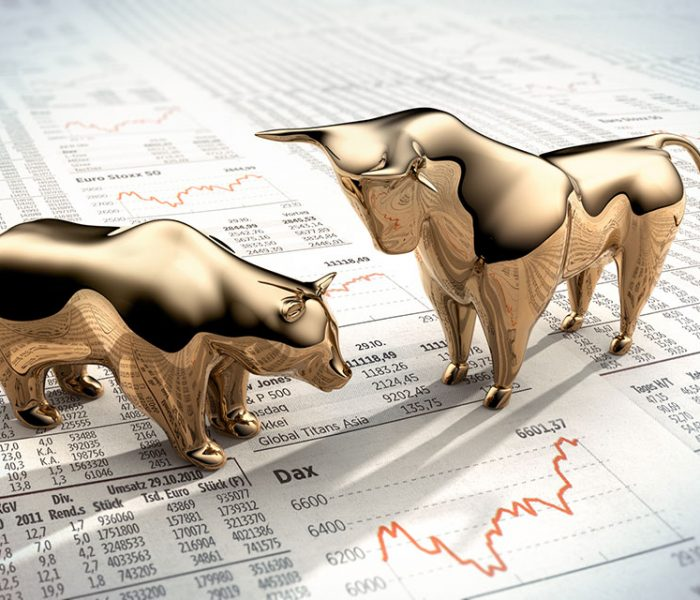 Golden symbolic figures on financial newspaper